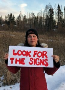 """Harmony Redsky holding """"Look For the Signs"""" poster"""