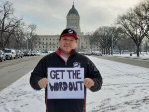 """Grand Chief Jerry Daniels holding sign that says """"Get the word out"""""""