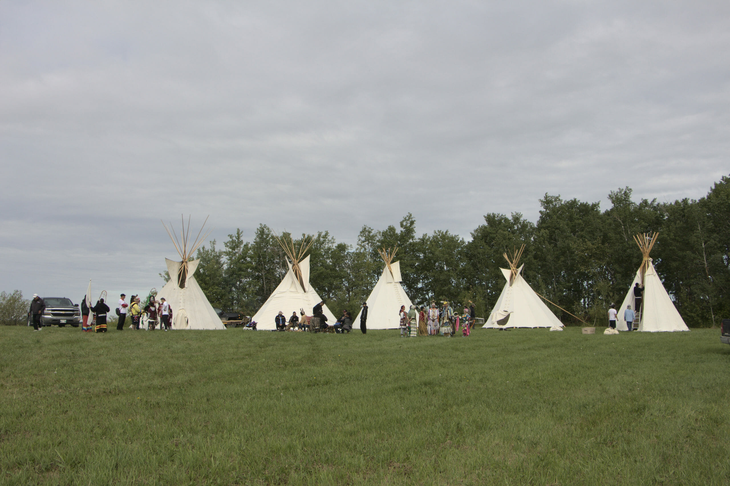 Five teepees set up and people dressed for ceremony